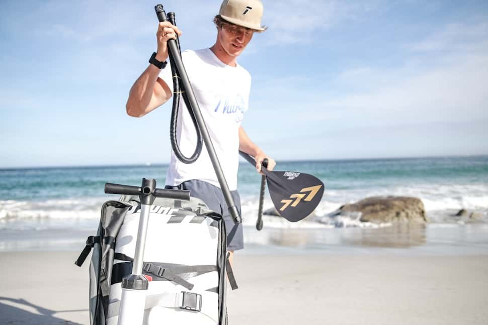 Young male paddleboarder on South African beach packing up his Thurso Surf Expedition Touring SUP and 3-piece adjustable paddle in an inflatable SUP roller backpack