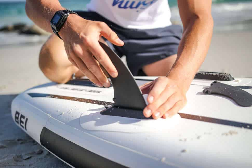 Young male paddleboarder attaches quick-lock fin to Thurso Surf Expedition Touring SUP