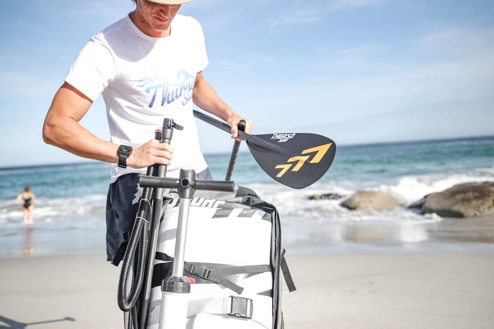 Young male paddleboarder unpacking Thurso Surf 3 piece adjustable paddle on a South African beach