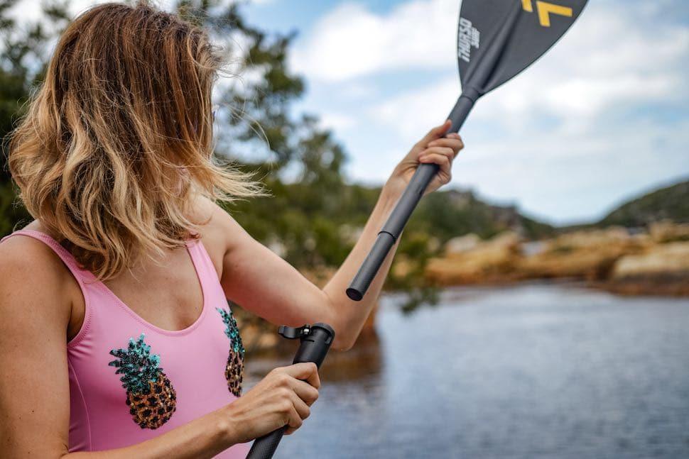 woman adjusts SUP paddle size