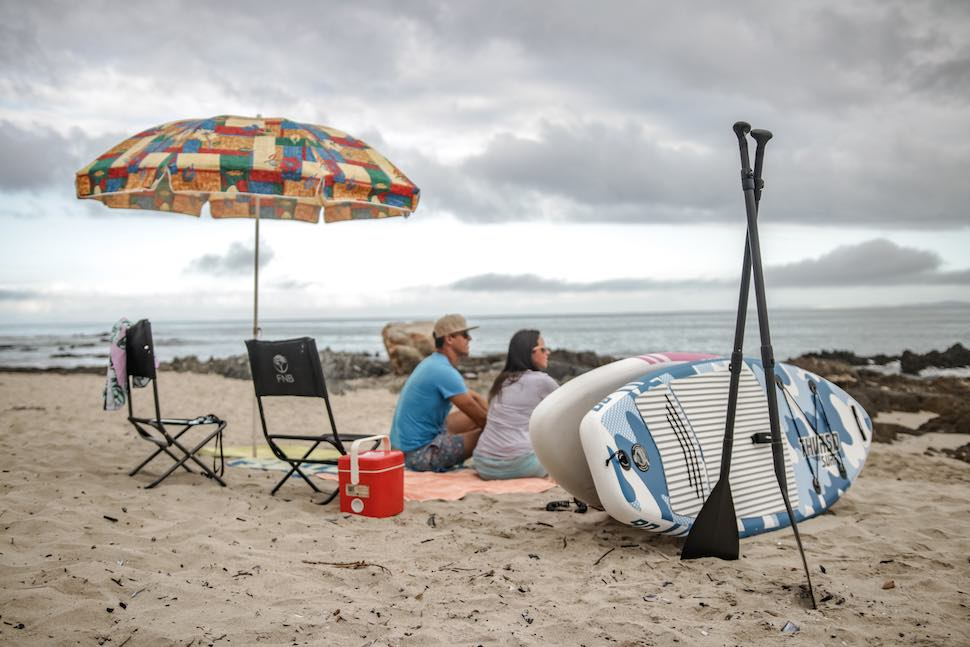 couple sitting on beach under umbrella near SUP paddles