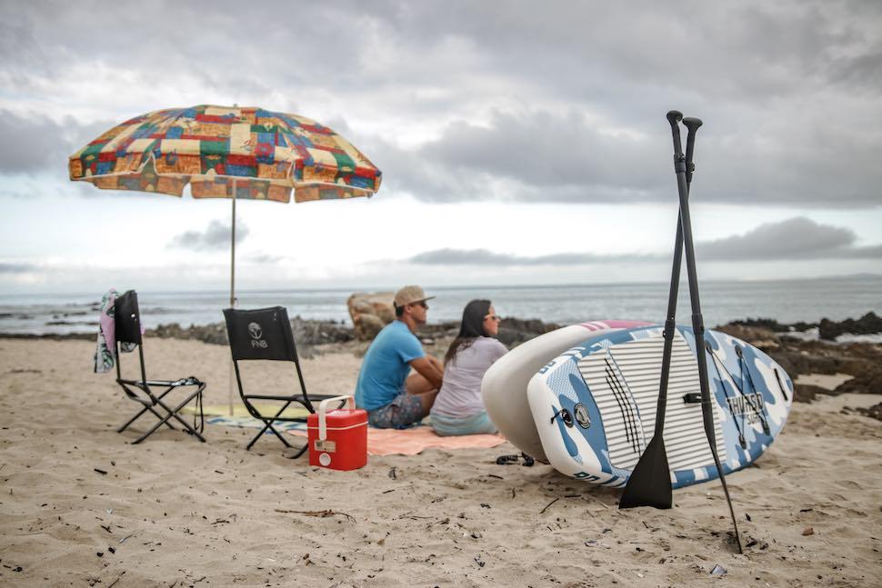 couple sitting on beach under umbrella near SUP paddles