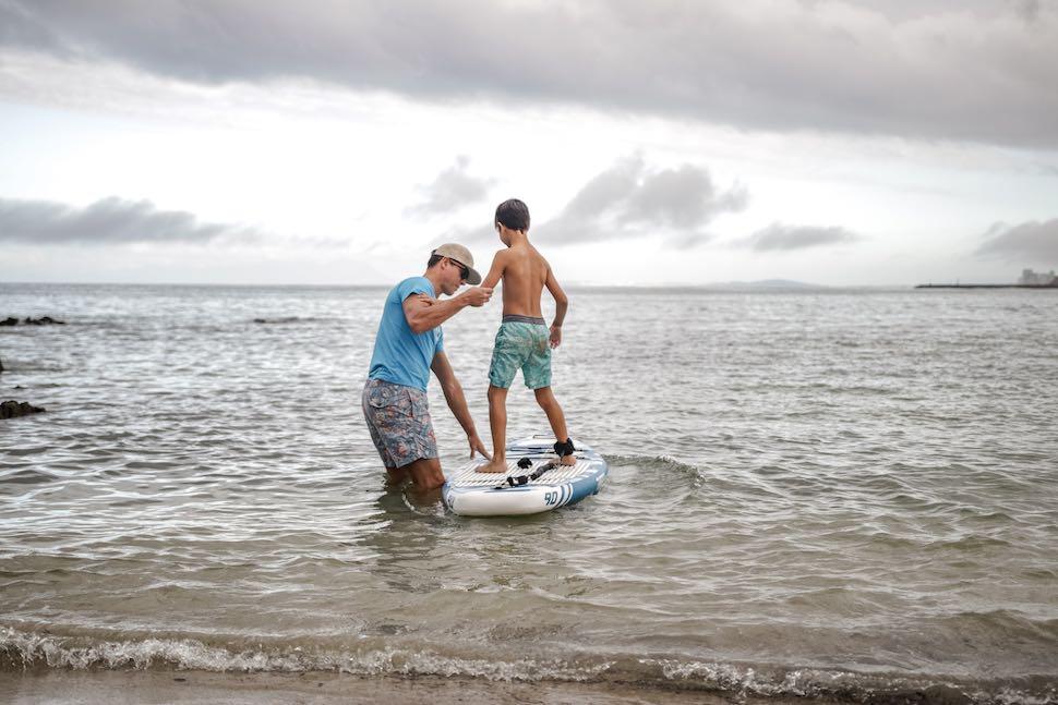 Man helping child get on Thurso Surf Prodigy Junior SUP