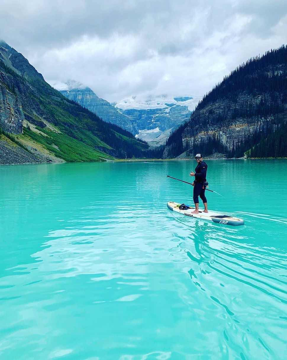 Man stand up paddleboarding bright blue glacial lake on Thurso Surf Expedition Touring SUP