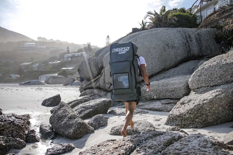 Man walking across rocks with Thurso Surf roller backpack