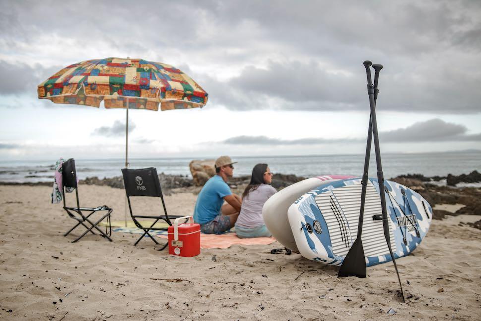 Couple sits on beach near Thurso Surf Prodigy Junior SUPs