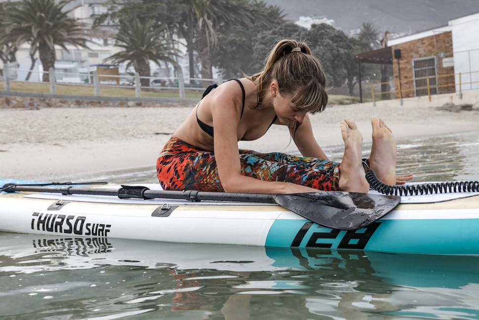 Thurso Surf Tranquility Yoga SUP being used for stretches by woman