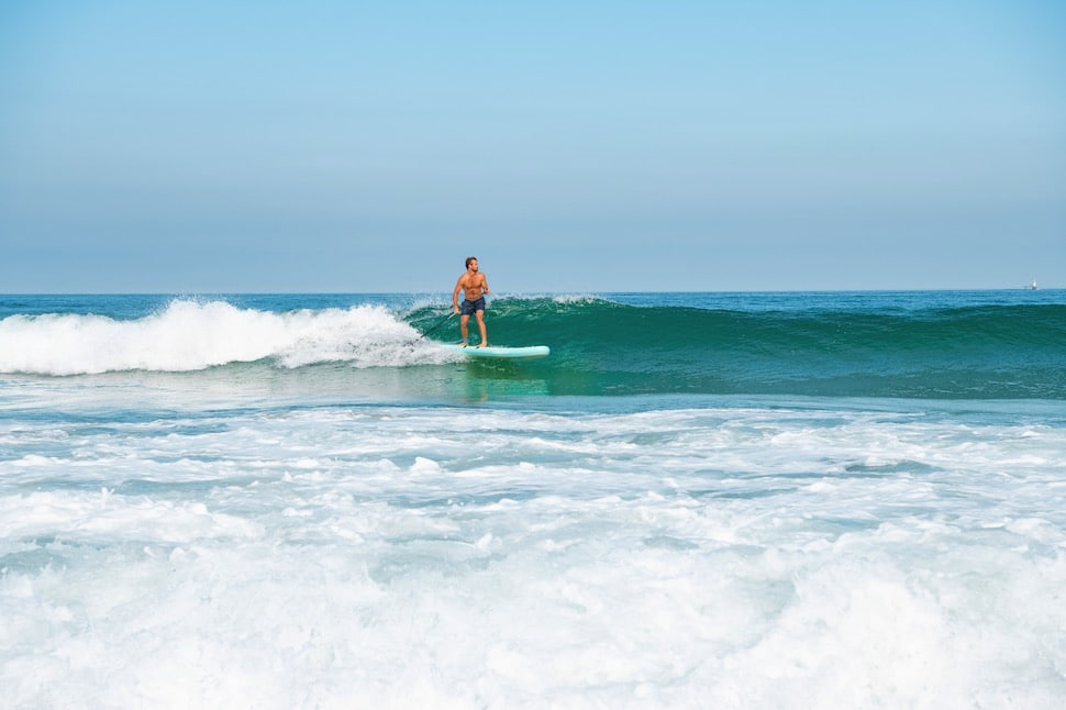 Stand up paddleboarder using an ankle leash while surfing