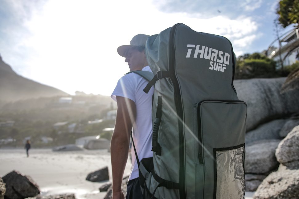 Man walks to beach with Thurso Surf Roller Backpack at one of the best places to go camping