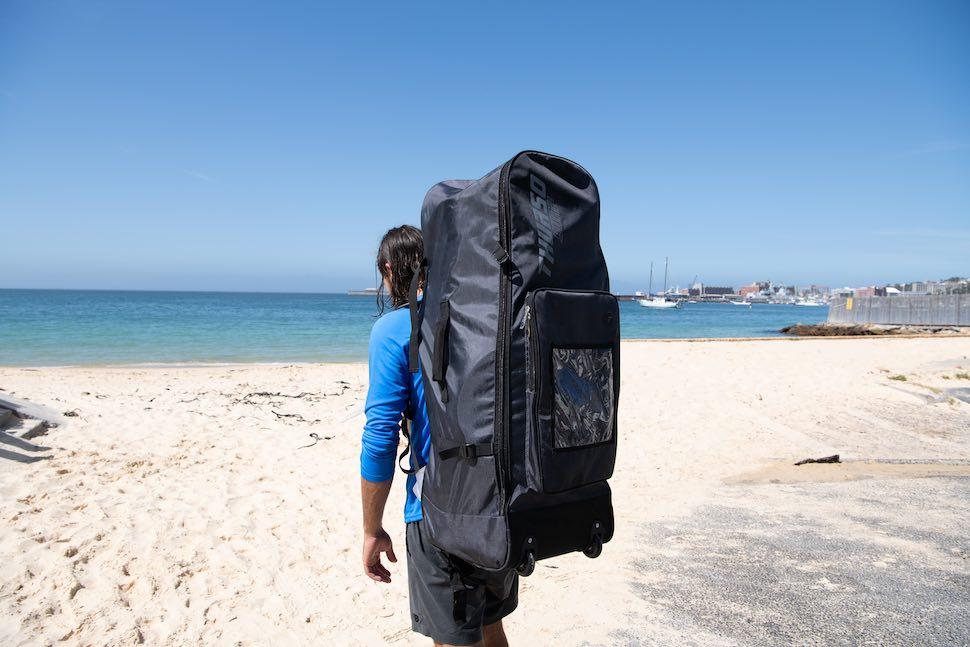 Man walks along beach with Thurso Surf Roller Backpack