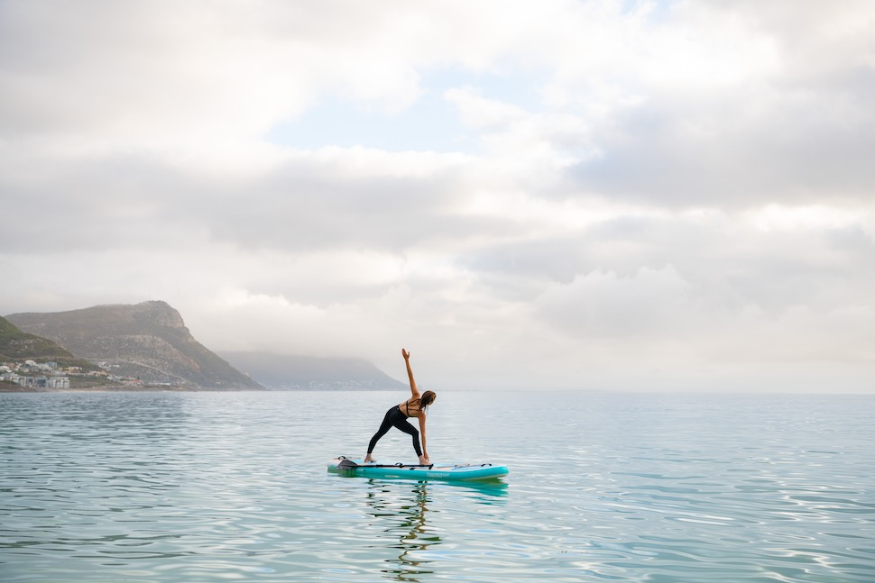 Woman performs yoga pose on Thurso Surf Tranquility Yoga SUP