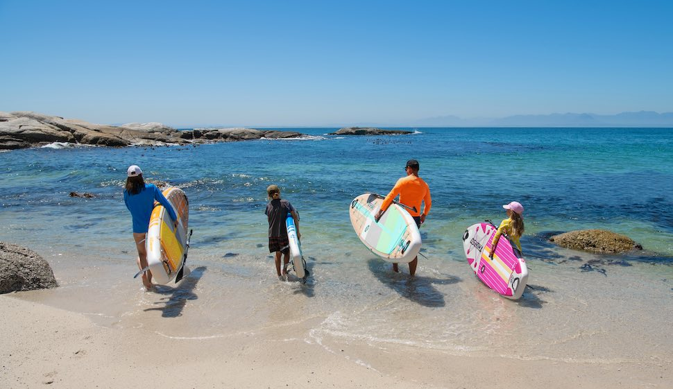 family carries Thurso Surf stand up paddleboards to the water