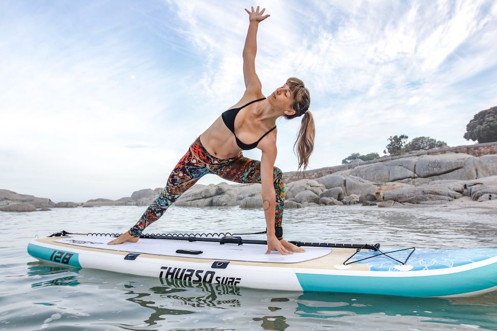stretching on a Thurso Surf Tranquility Yoga SUP in open water