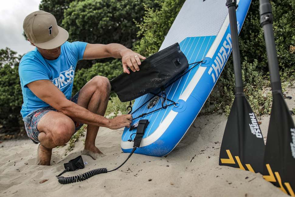man attaches Thurso Surf deck cooler bag to tail of board with easy clip attachments