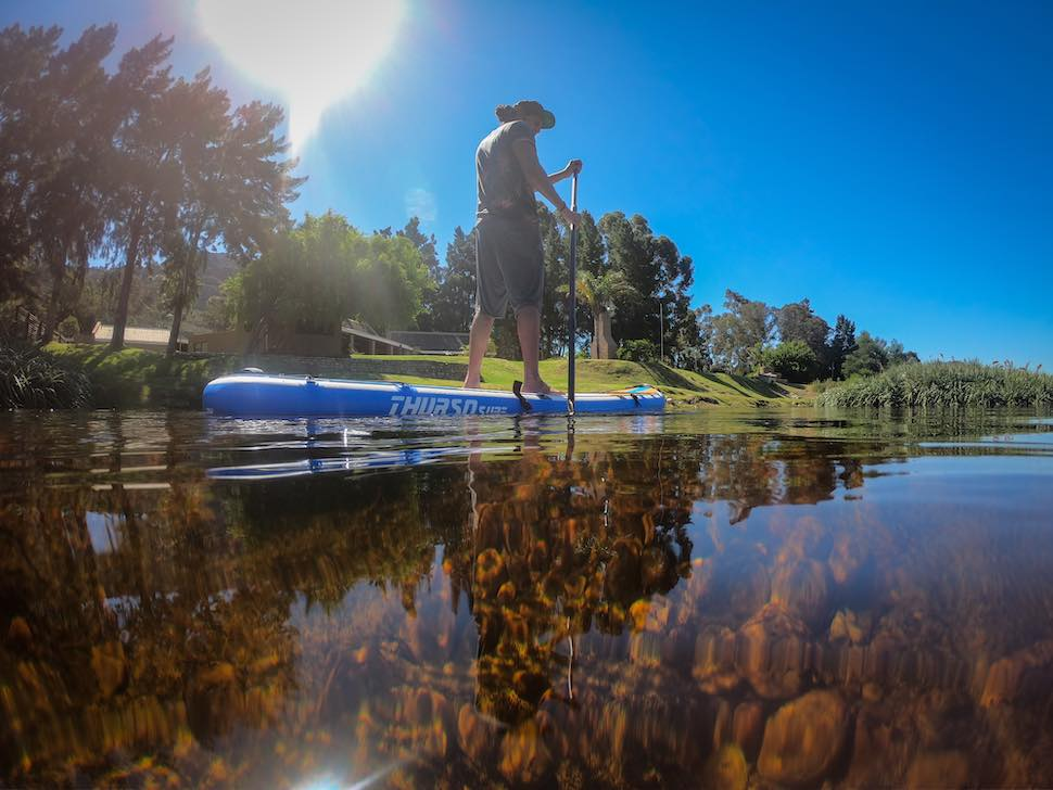 man paddles Thurso Surf Max multi-purpose SUP down clear river