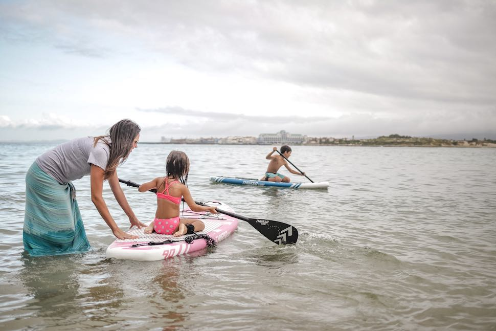 best women's paddle board article - woman plays with kids near beach with kids on Thurso Surf Junior Prodigy Stand Up Paddleboard