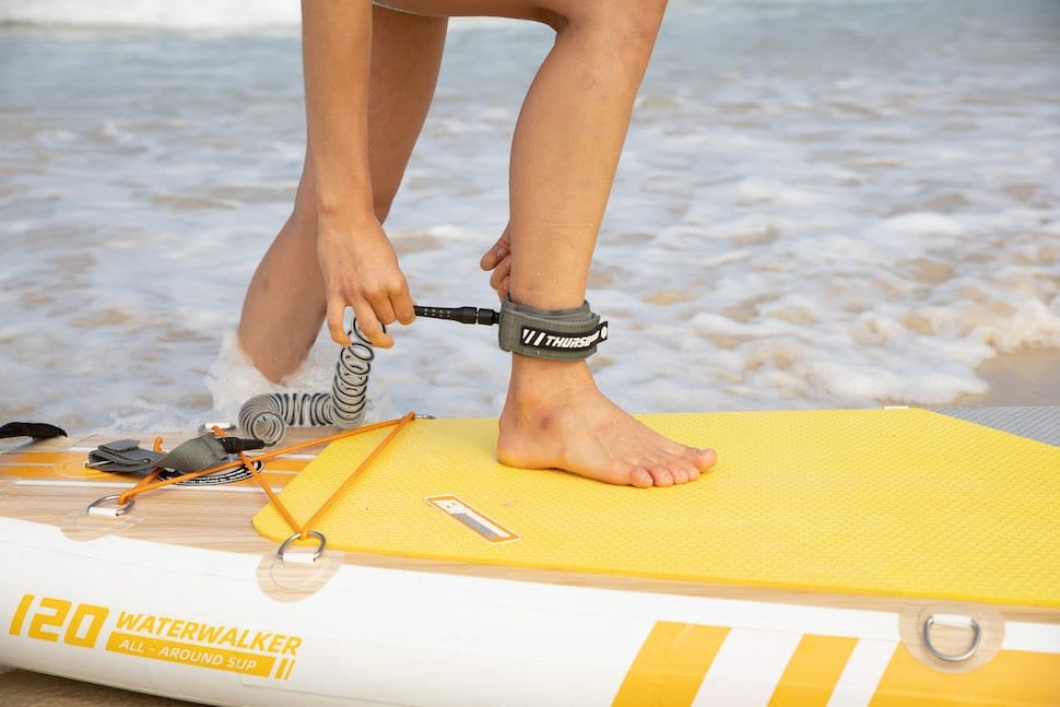 woman attaches stand up paddle board leash to ankle