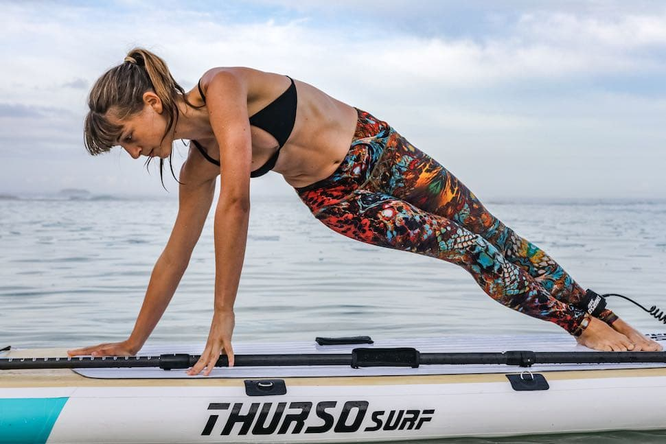 woman wears yoga pants for her stand up paddle clothes while doing a workout
