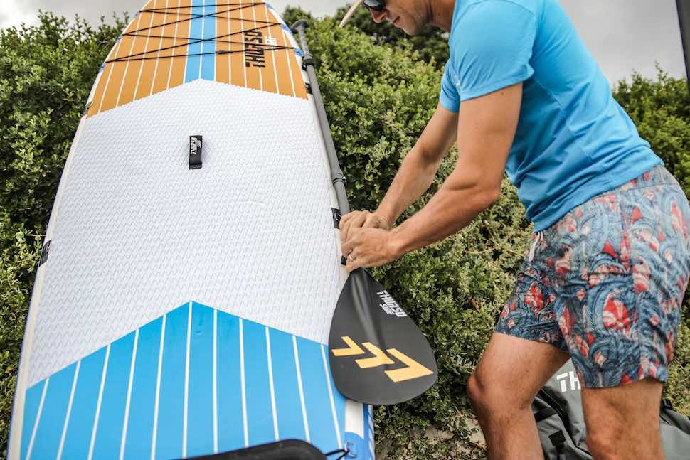 man shows how to transport a paddle board paddle by attaching it to his Thurso Surf Max multi-purpose SUP