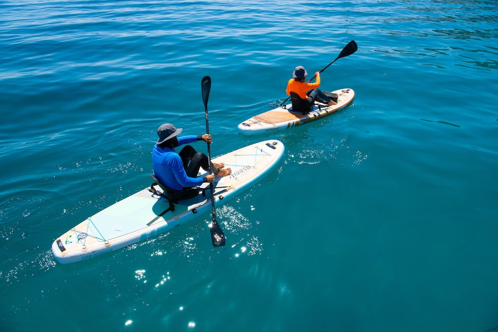 Man and woman sitting on stand up paddle board traction pad while SUP kayaking