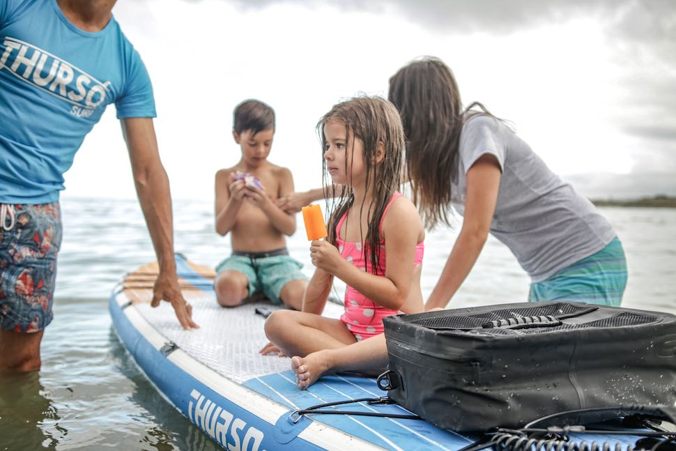 Family enjoys snack while sitting on stand up paddle board traction pad