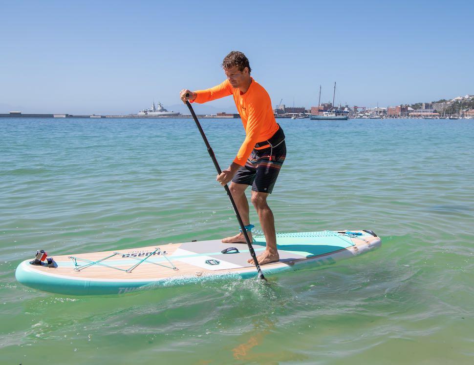 Man in orange shirt paddles on Thurso Surf Waterwalker All-around SUP near coastline