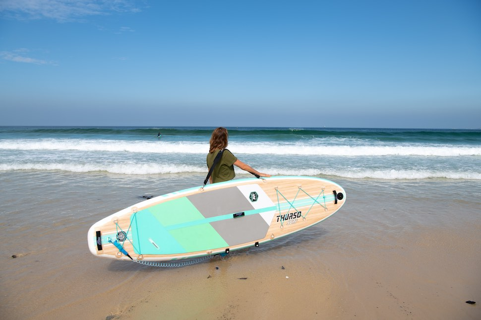 woman on beach stand with Thurso Surf Waterwalker All-around SUP while overlooking the ocean
