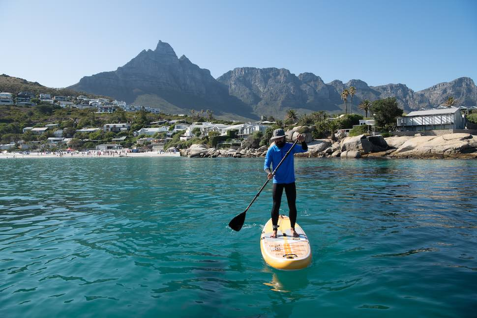man on SUP exercises by paddling for fun