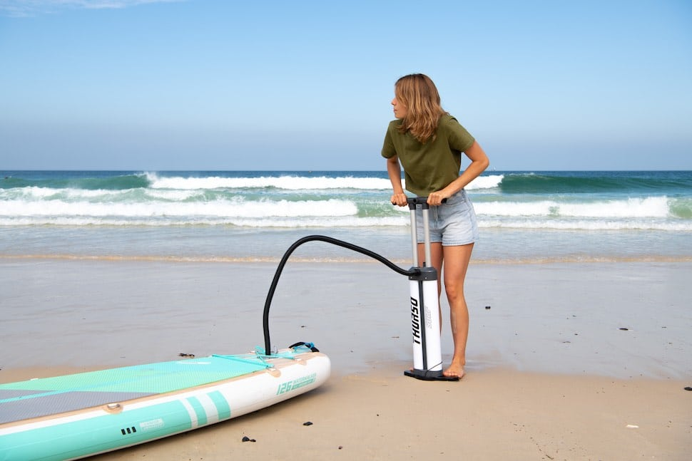 woman inflates her Thurso Surf iSUP before her SUP exercise