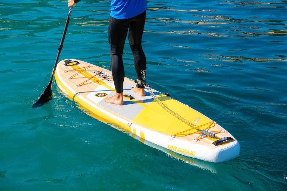 closeup of man paddling on Thurso Surf Waterwalker All-around SUP with yellow stand up paddleboard traction pad
