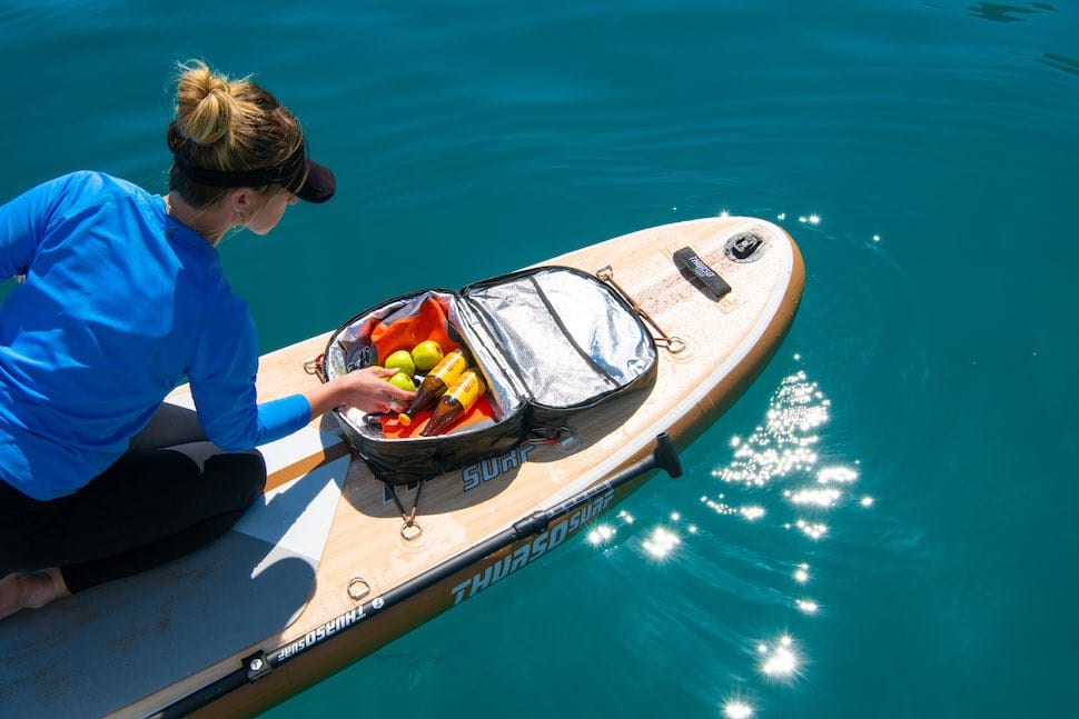 woman kneeling on stand up paddleboard traction pad while looking into Thurso Surf Deck Cooler Bag