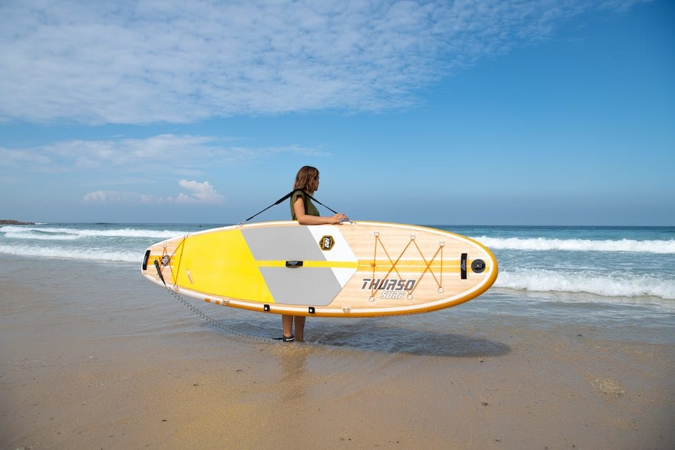 Woman reads the waves to SUP surf safely before paddling out