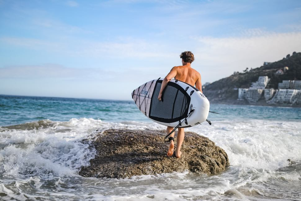 Man walks in ocean from beach carrying Thurso Surf Expedition Touring SUP